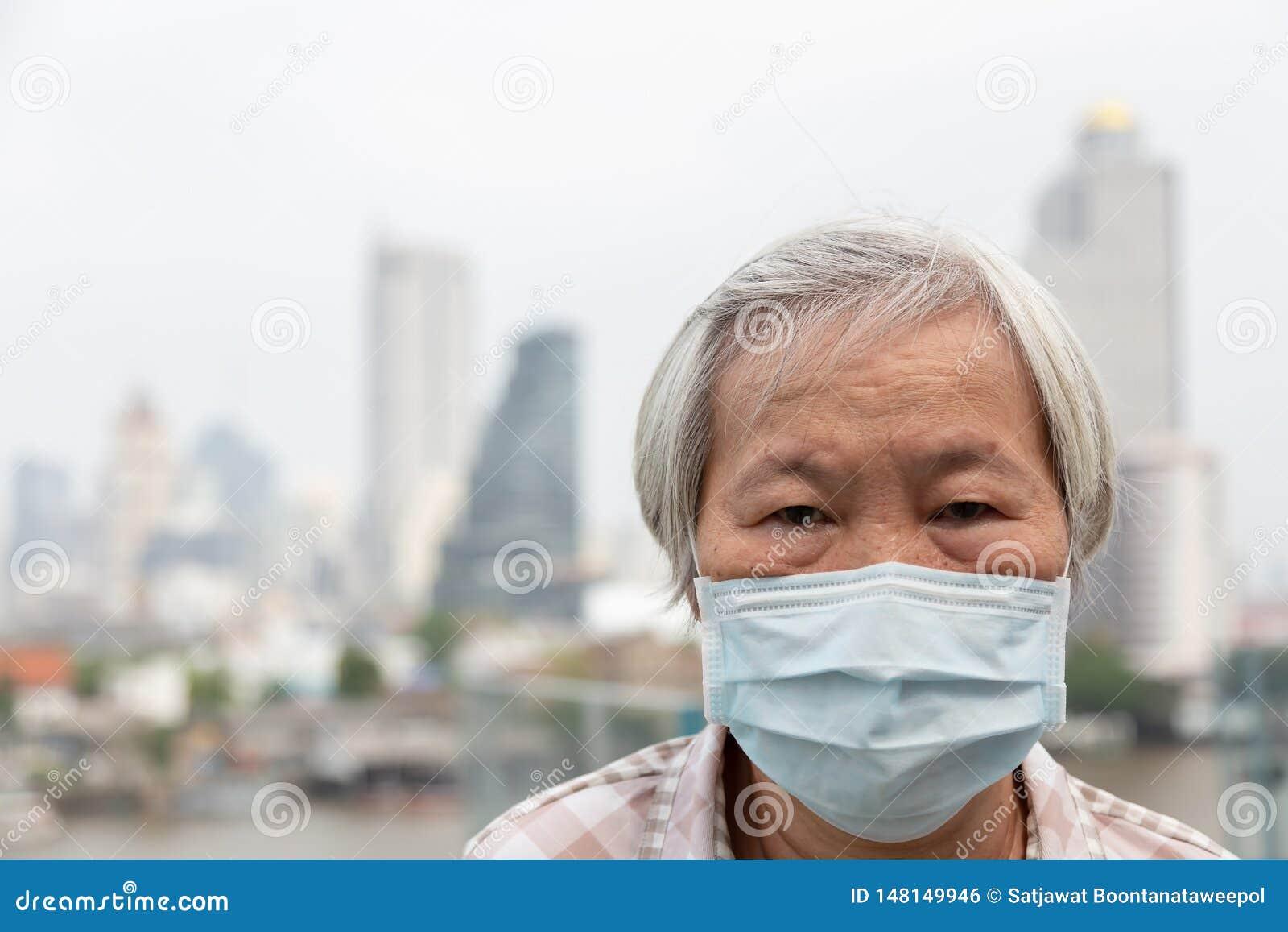 Asiatisk h?g kvinna med skydd f?r framsidamaskering, b?rande framsidamaskering f?r ?ldre kvinna p? grund av luftf?rorening i stad