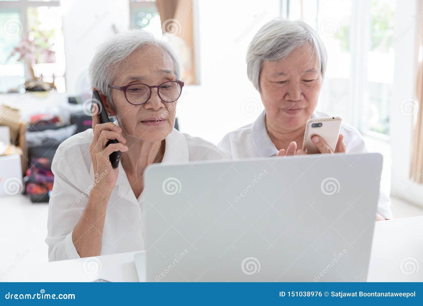 Asiatisk hög kvinna och vän med bärbar datordatoren, lyckligt le äldre folk som håller ögonen på något intressera, medan rymma