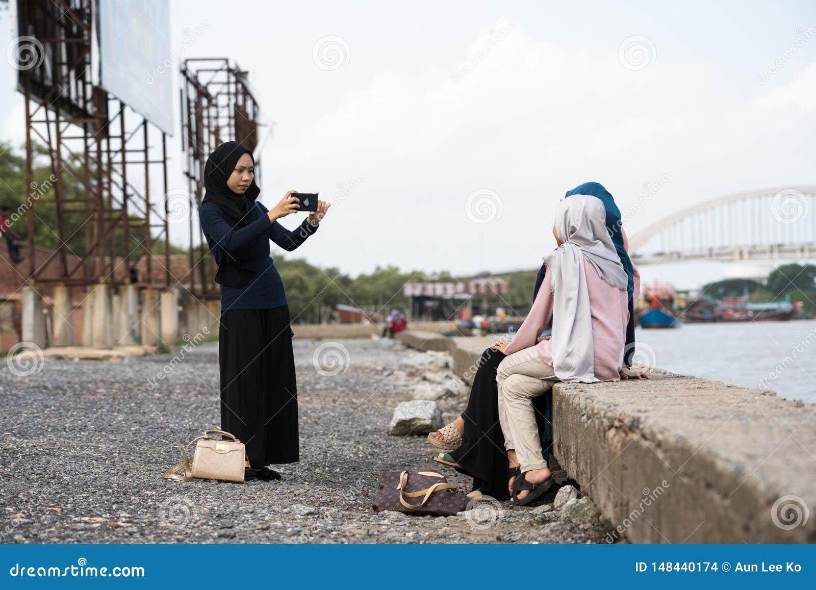 Asiatisk hijabflicka som tar fotoet
