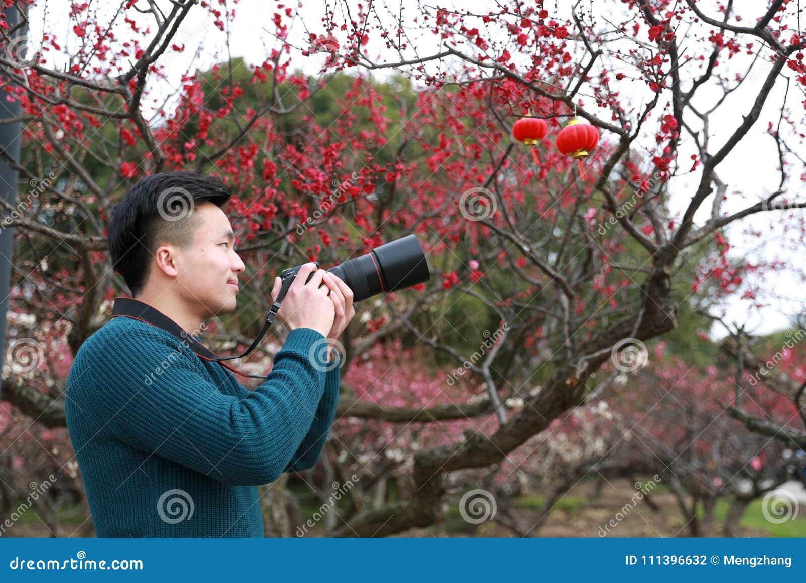 Asiatisk kinesisk manfotograf i natur