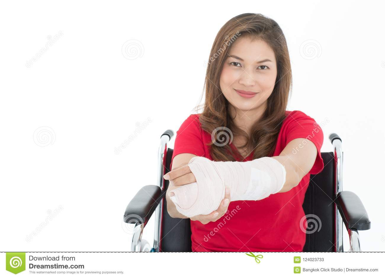Asiatisk kvinna för bruten arm med gipsförbandet i henne händer som sitter på