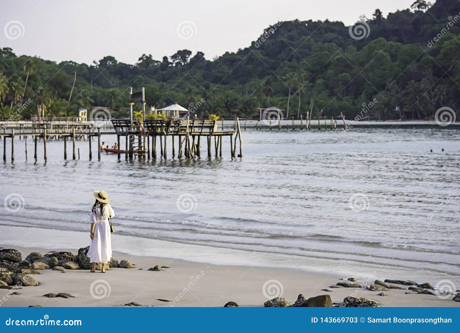 Asiatisk kvinna på stranden bakgrundshavet och en träbro på Koh Kood, Trat i Thailand