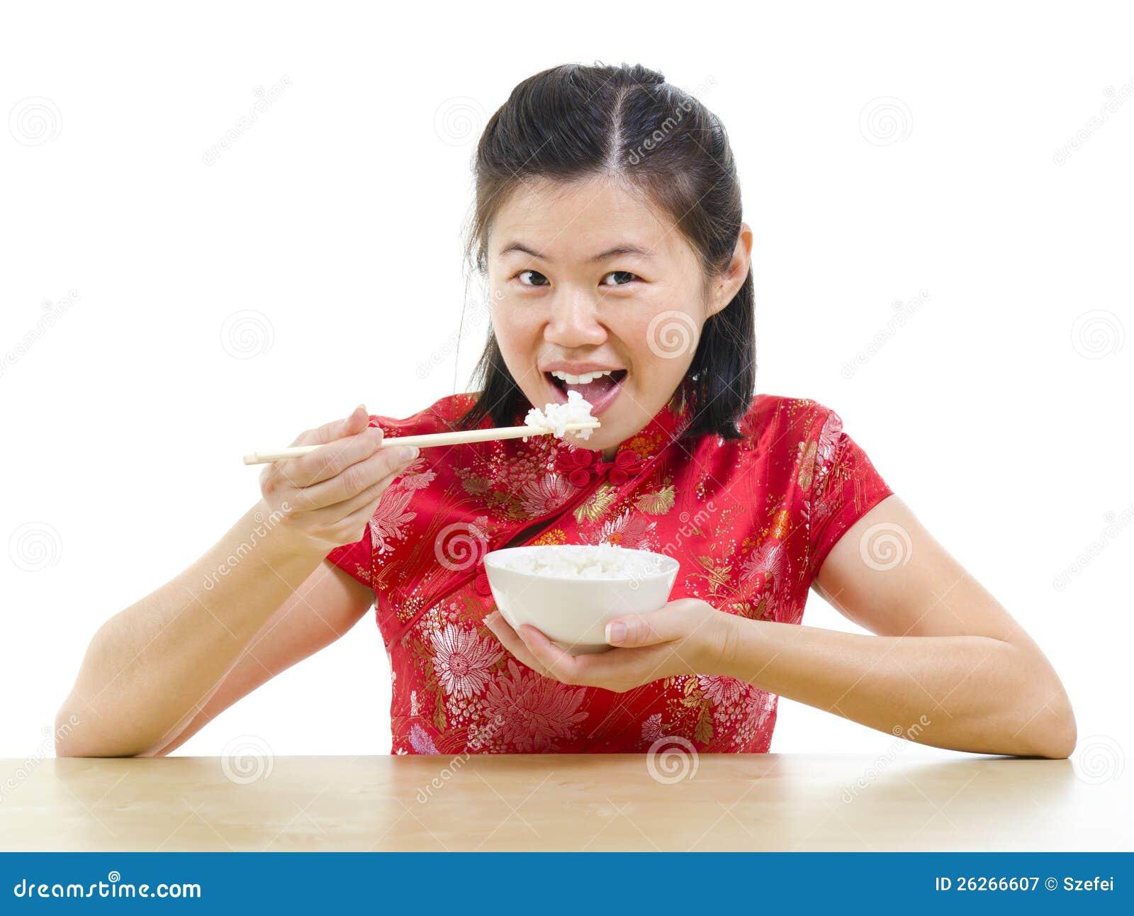 Asiatisk kvinna som äter rice