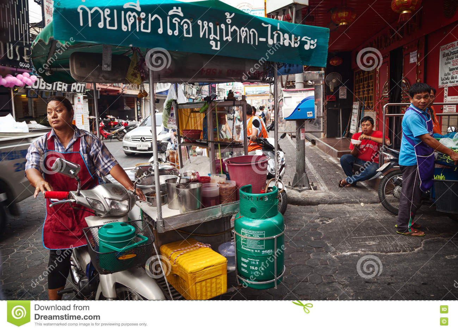Asiatisk kvinna som kör en matvagn som säljer gatamat Mobil thailändsk matförsäljare