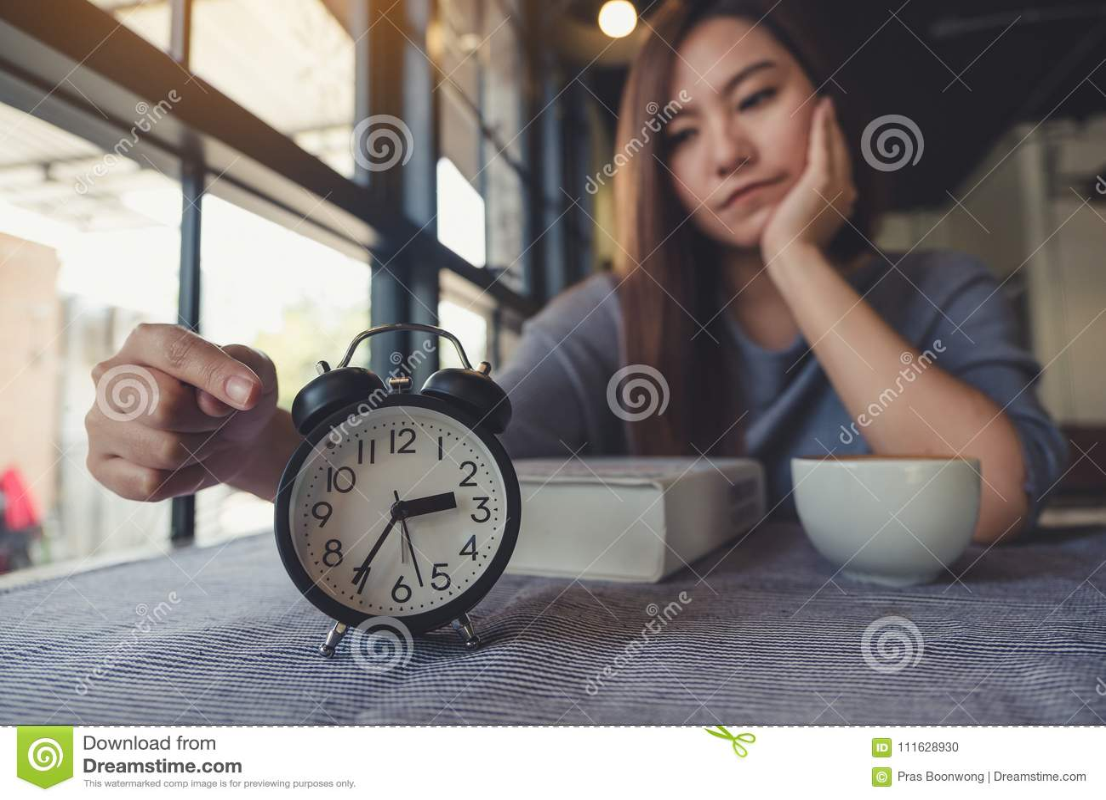 Asiatisk kvinna som pekar på en svart klocka med borrad känsla, medan vänta på någon
