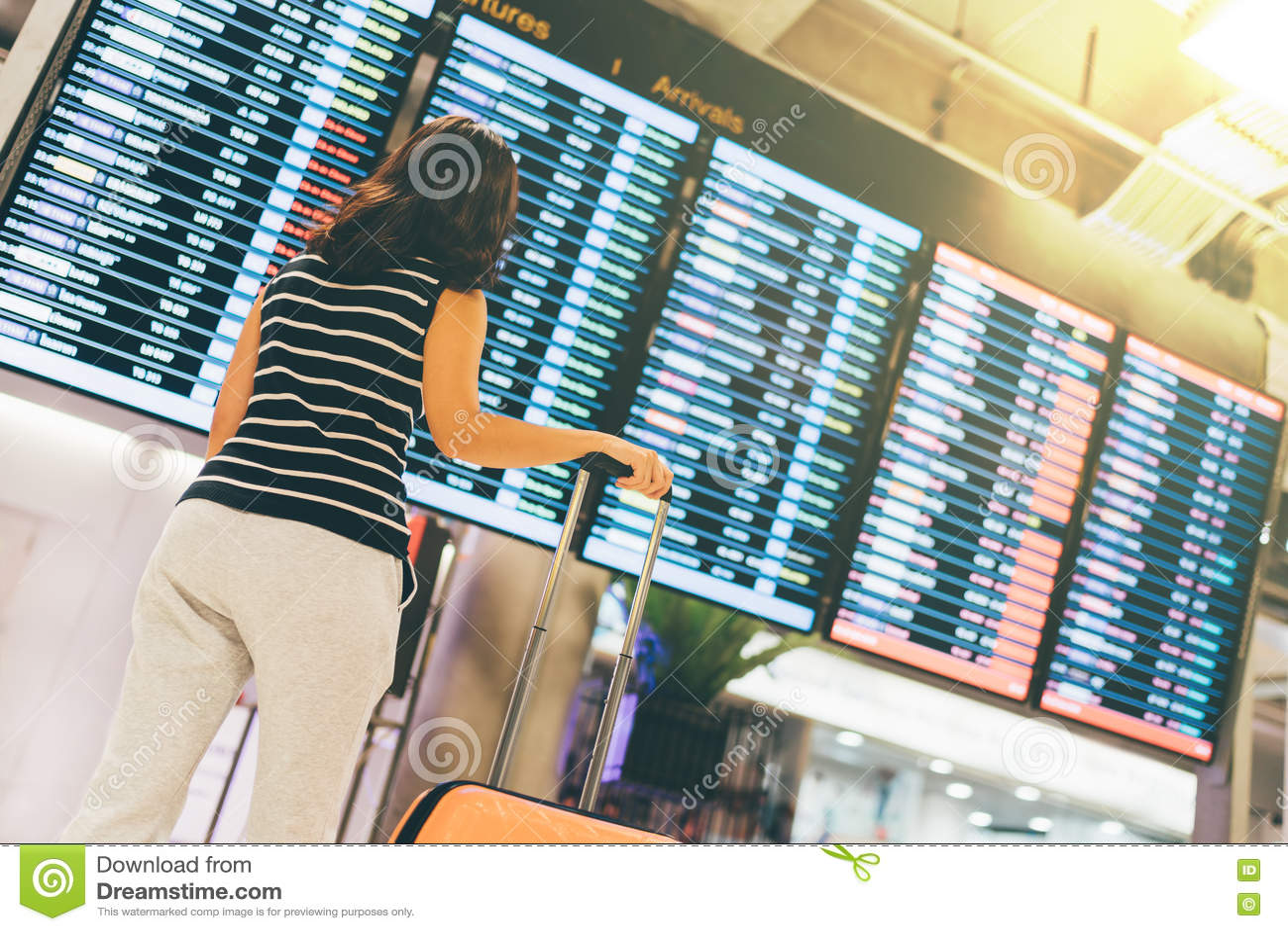 Asiatisk kvinnahandelsresande som ser informationsskärmen om flyg i en flygplats, ett hållande resväska-, lopp- eller tidbegrepp