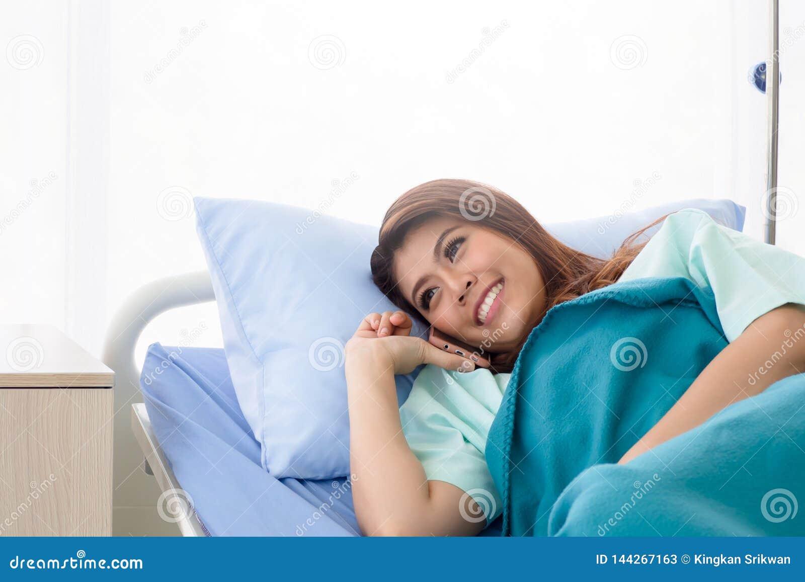 Asiatisk kvinnapatient som använder mobiltelefonen på säng som medges i sjukhus