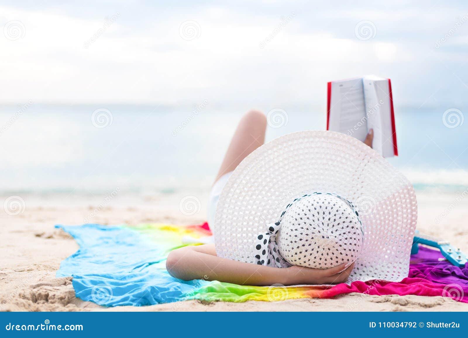 Asiatisk kvinnasolbadning och läseböcker i ferie på stranden B