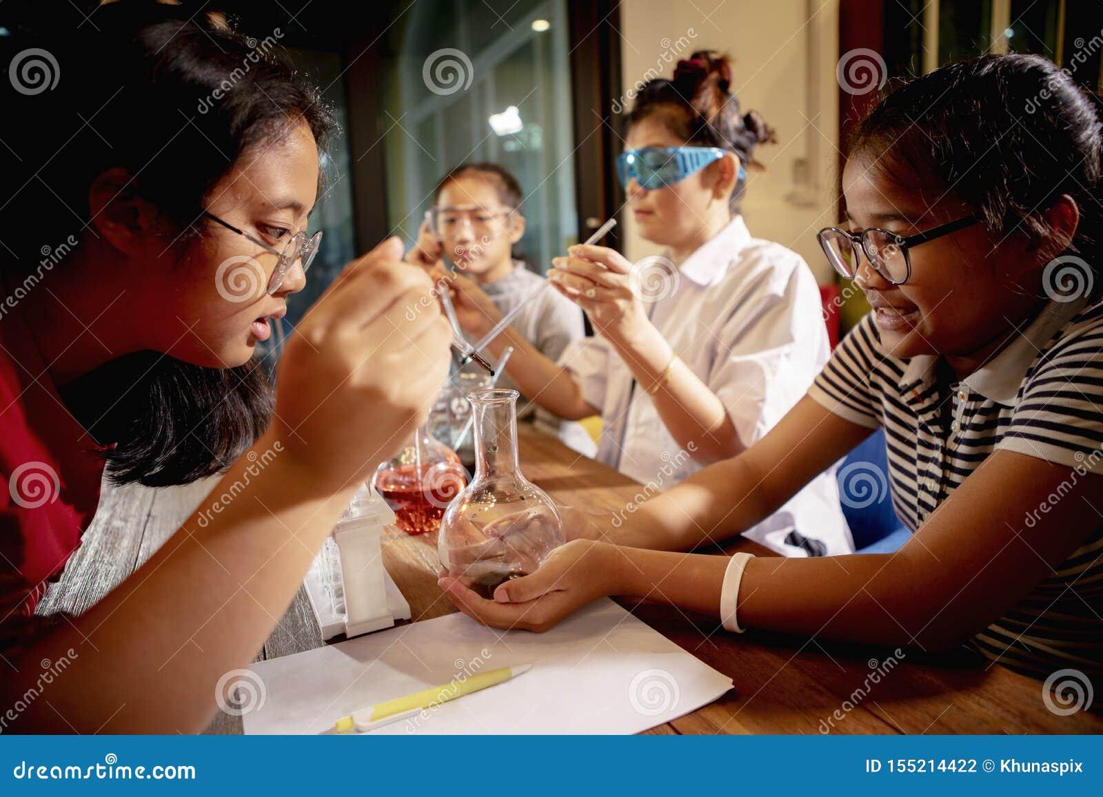 Asiatisk lärare och student i rum för skolavetenskapslaboratorium