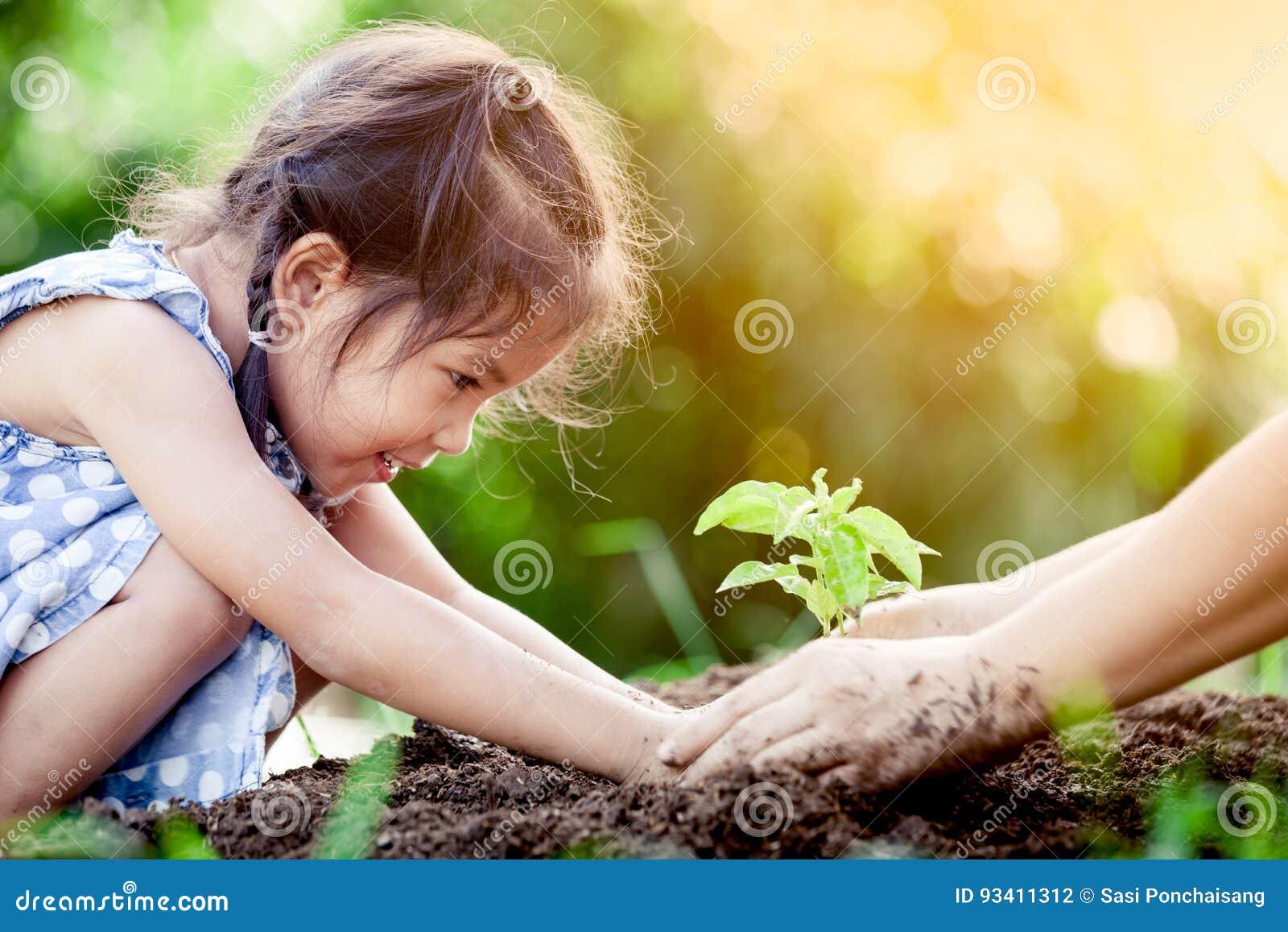 Asiatisk liten flicka och förälder som planterar det unga trädet på svart jord