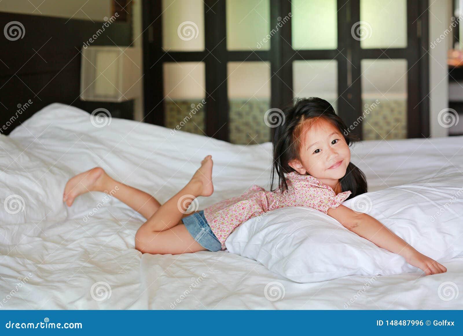 Asiatisk liten kinesisk flicka som hemma ligger p? s?ngen med att se kameran