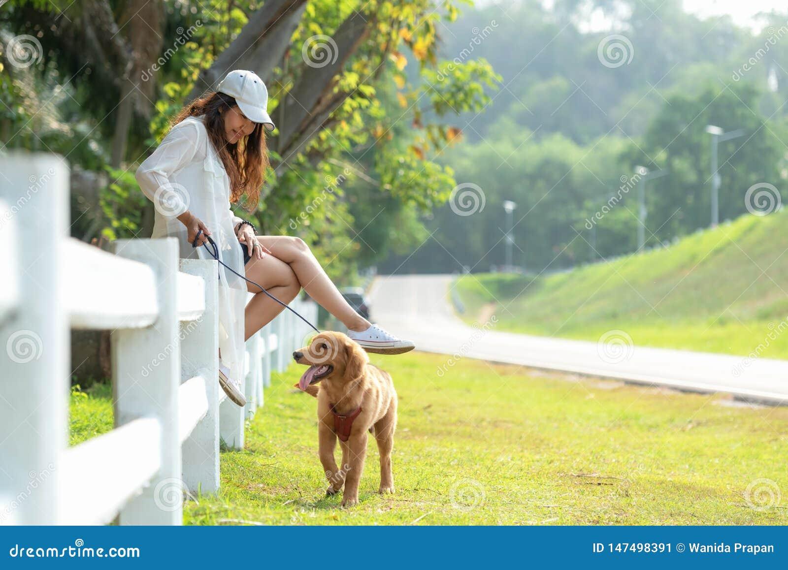 Asiatisk livsstilkvinna som spelar med golden retrieverkamratskaphunden i soluppgång