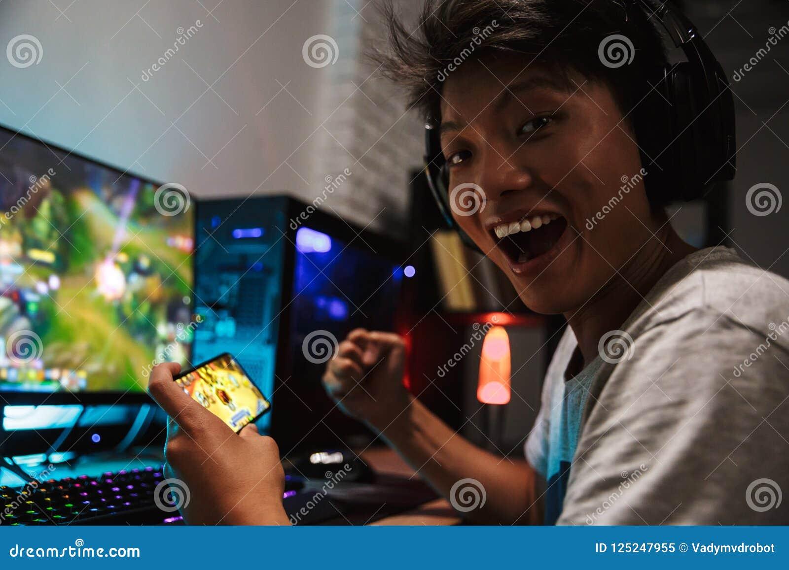 Asiatisk lycklig gamerpojkefröjd, medan spela videospel på sma