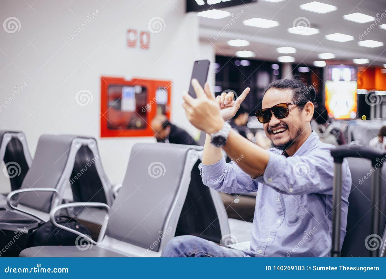 Asiatisk man med ryggsäckhandelsresanden som använder den smarta mobiltelefonen för den videopd appellen och tar på en flygplats