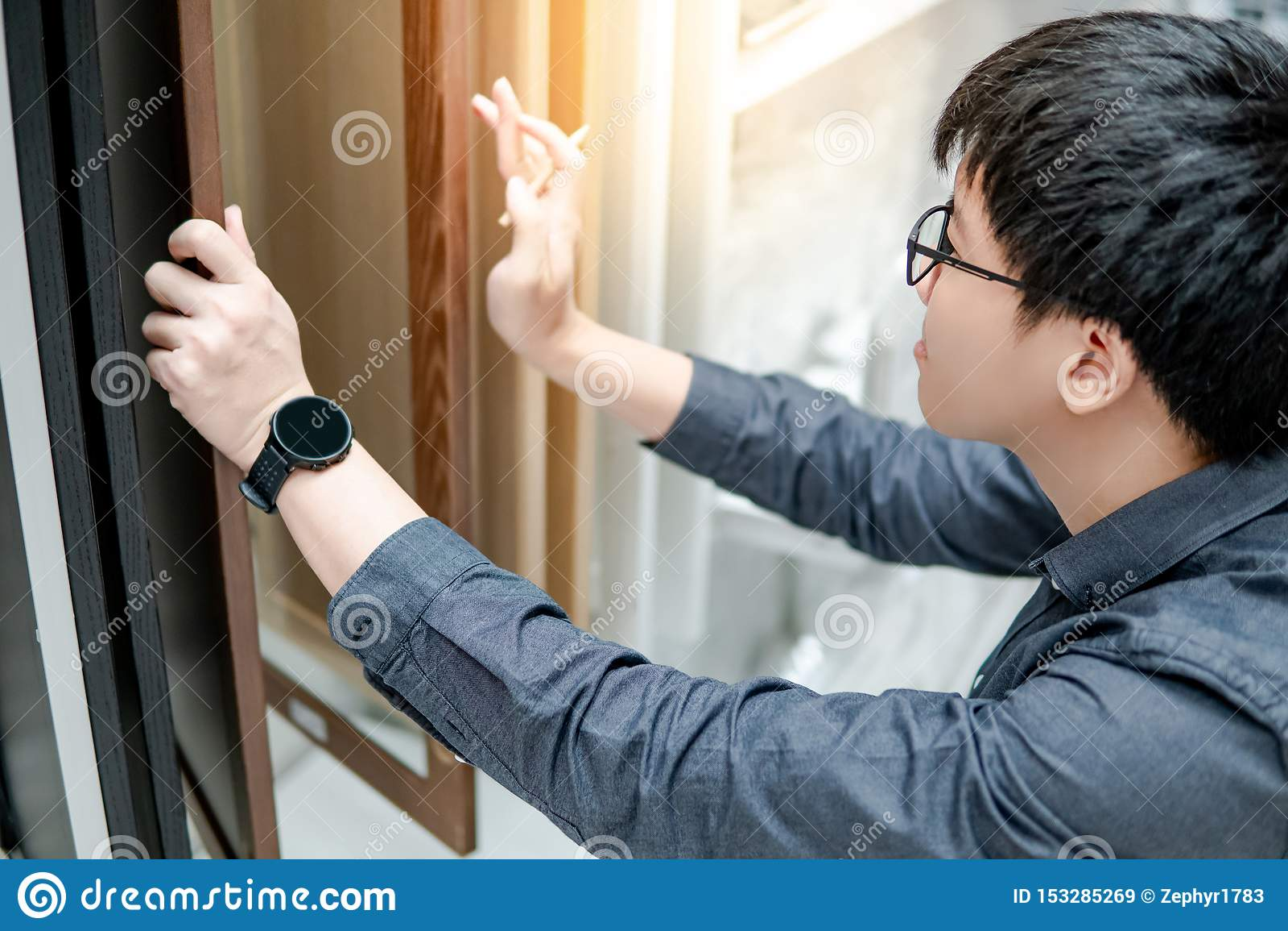 Asiatisk man som väljer kabinett- eller countertopmaterial