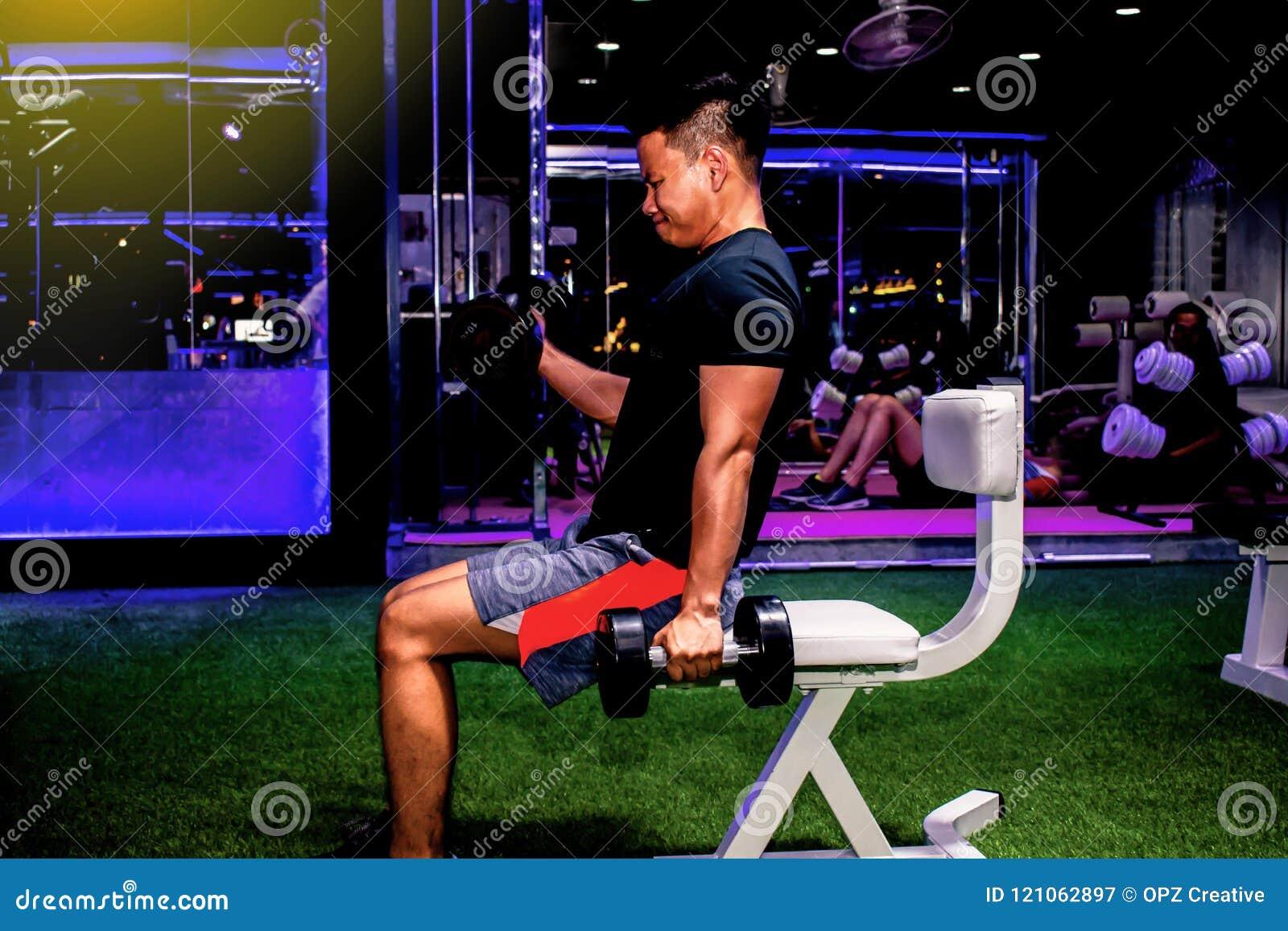 Asiatisk mankroppsbyggare med stiligt idrotts- för hantelviktmakt
