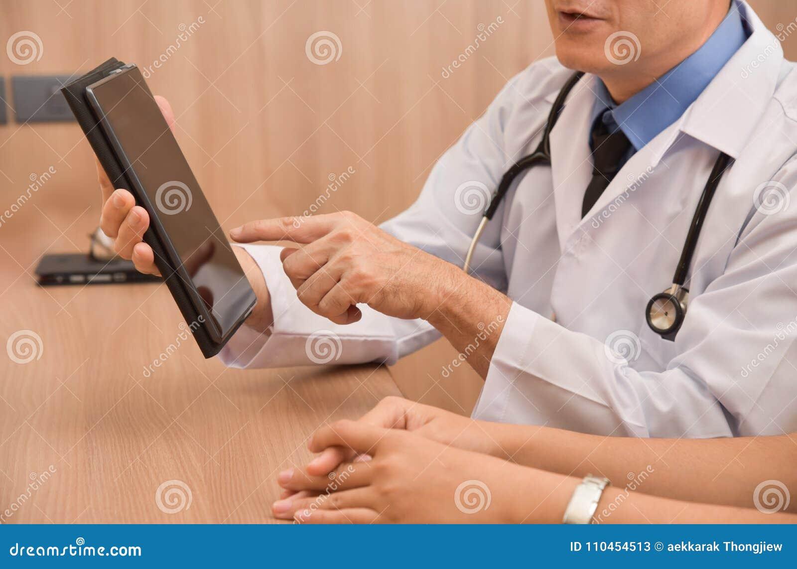 Asiatisk manlig doktor som använder den digitala minnestavladatoren