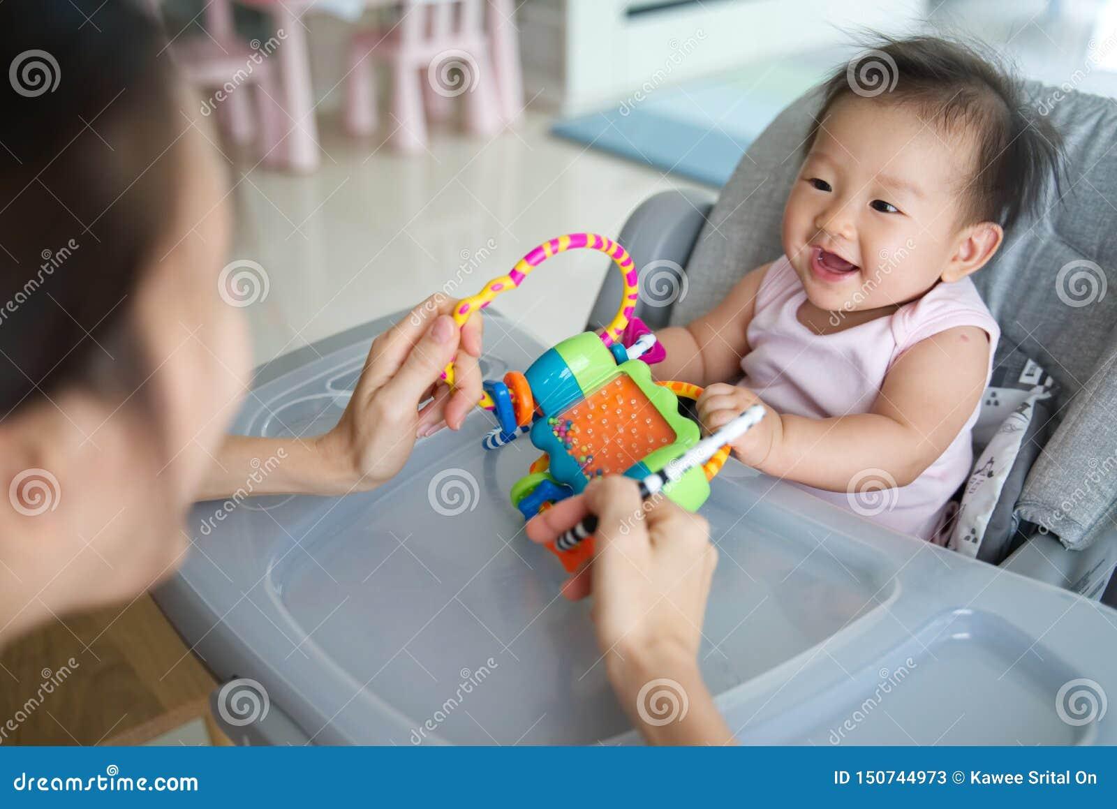 Asiatisk moder som spelar för att leka med henne för att behandla som ett barn att sitta på den dinning stolen hemma De är tycker