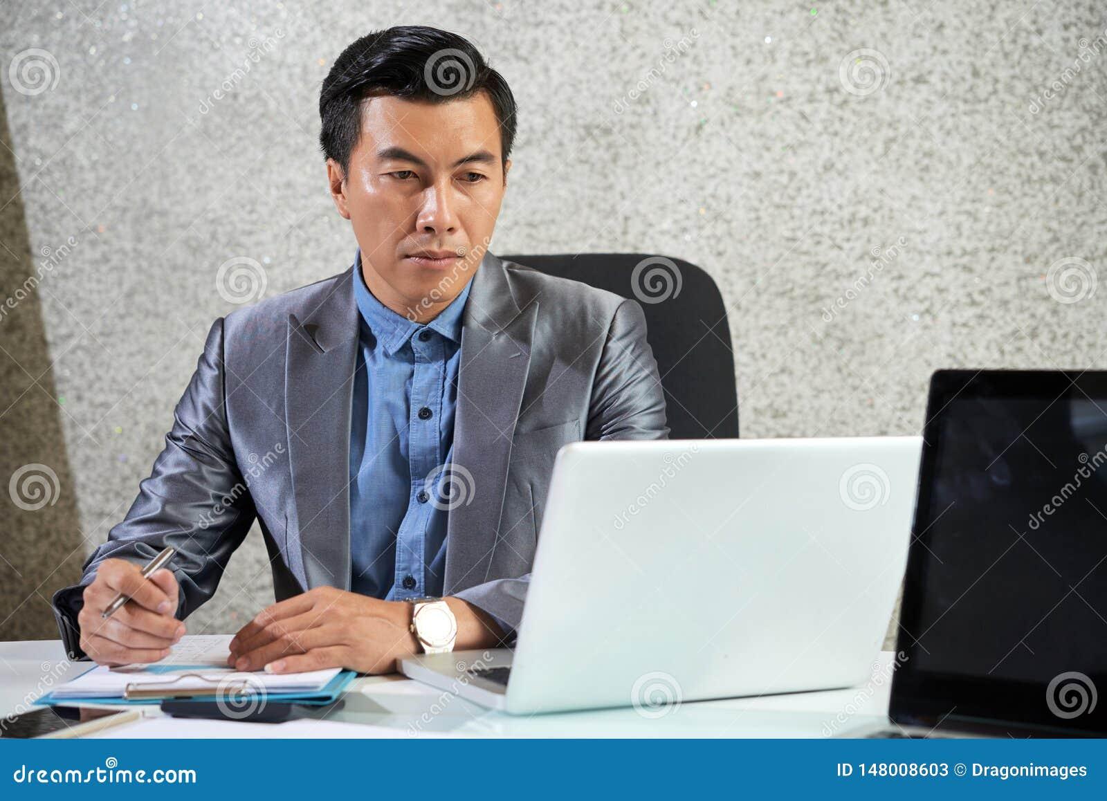 Asiatisk mogen affärsman som arbetar på bärbara datorn på kontoret