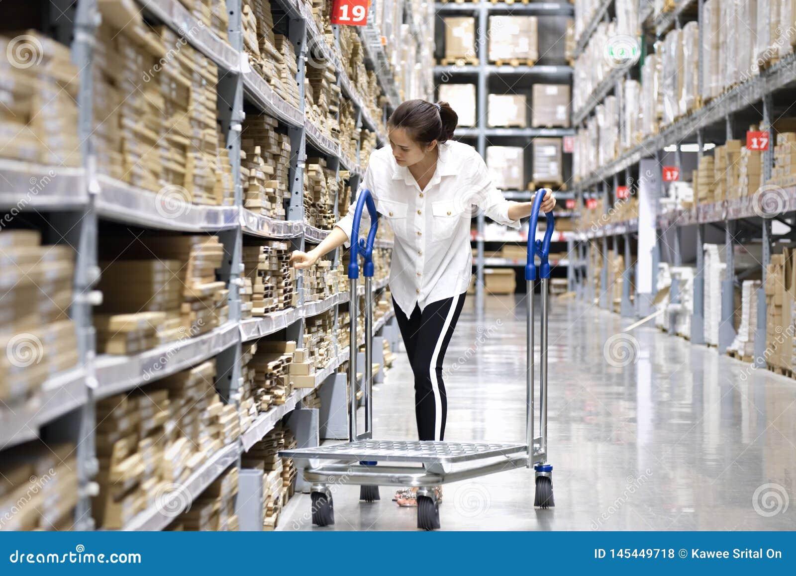 Asiatisk n?tt kund som s?ker produkter i lagerlager Flickan som anv?nder hennes handpunkt till etiketten f?r att kontrollera numr