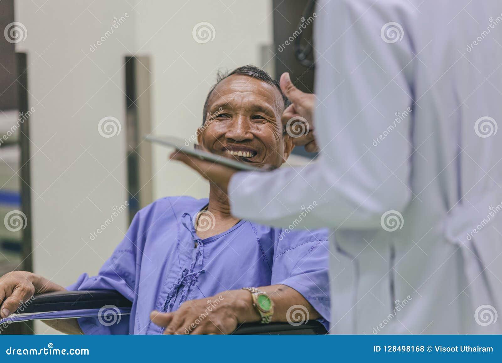 Asiatisk patient i rullstolsammanträde i sjukhus med asiatisk docto