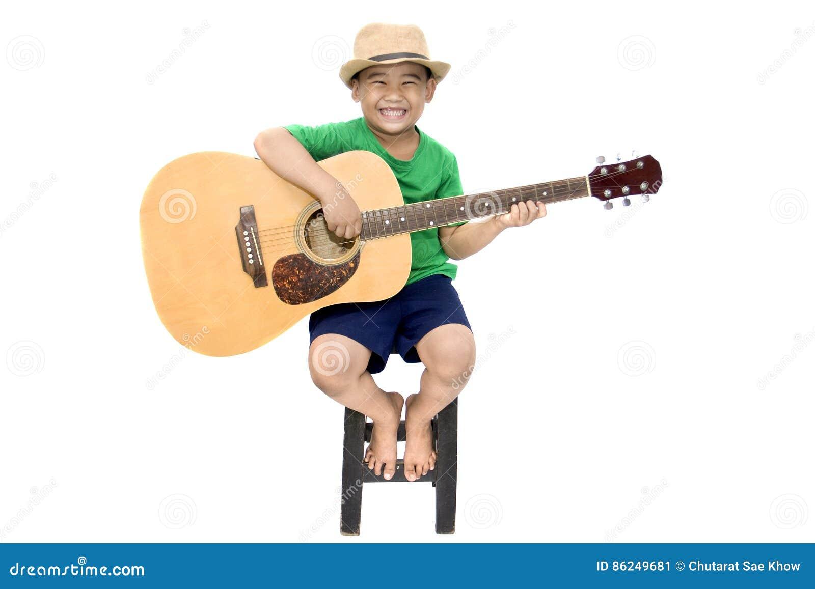 Asiatisk pojke som spelar gitarren på isolerad vit bakgrund