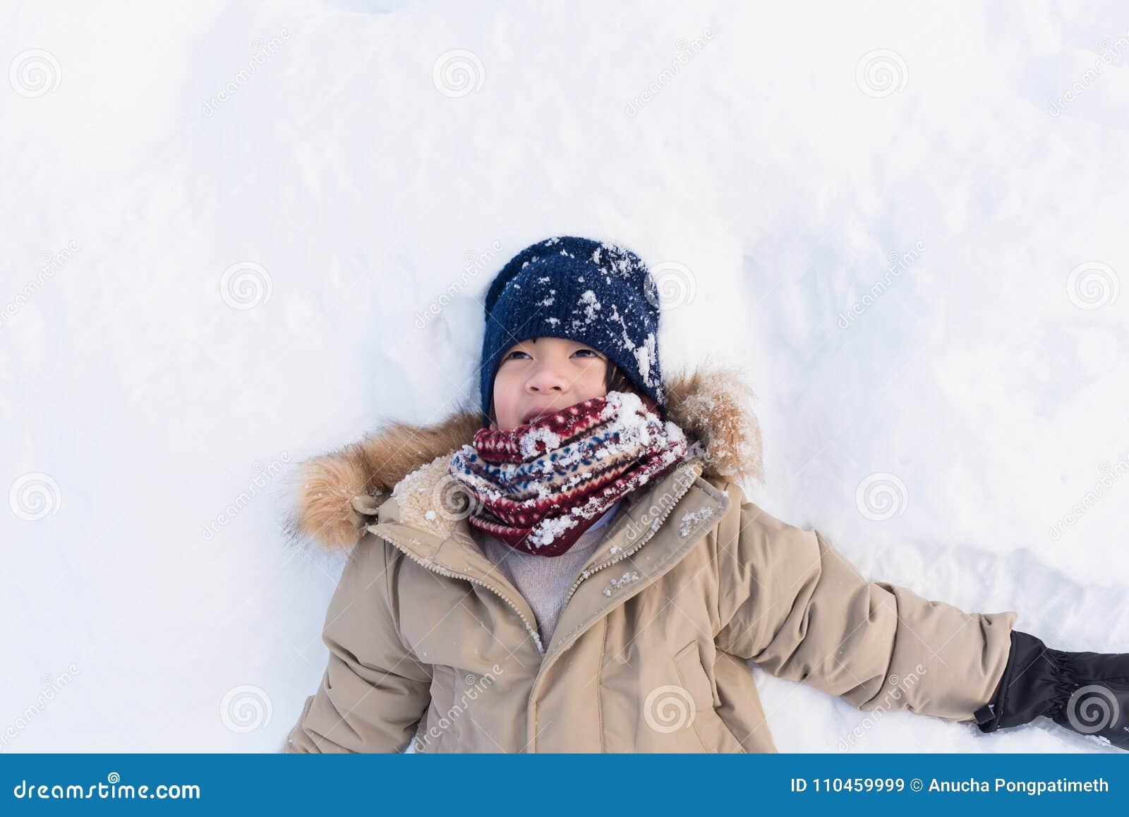 Asiatisk pojke som spelar snö