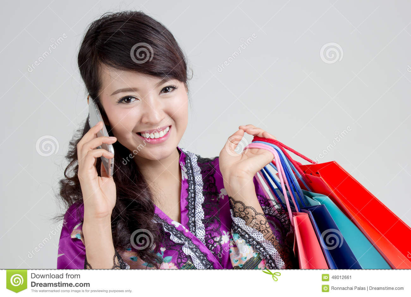 Asiatisk shoppingkvinna som använder den smarta telefonen