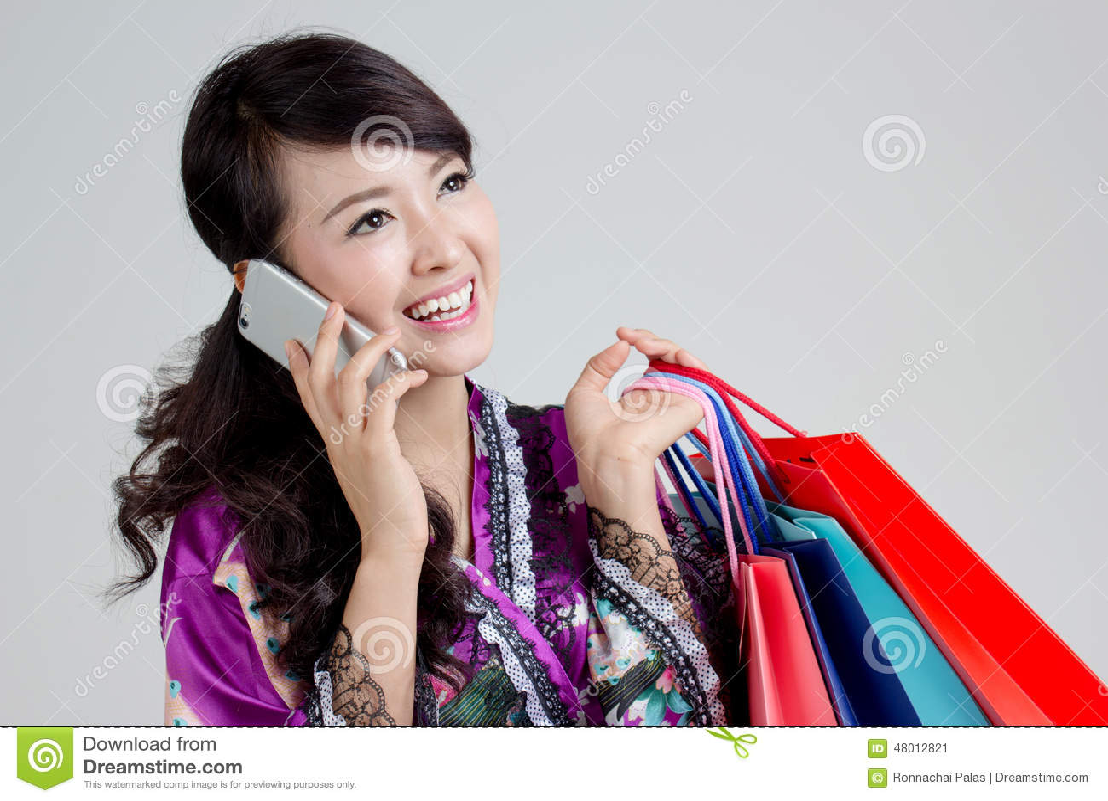 Asiatisk shoppingkvinna som använder smarta färgrika shoppingpåsar för telefon och för innehav