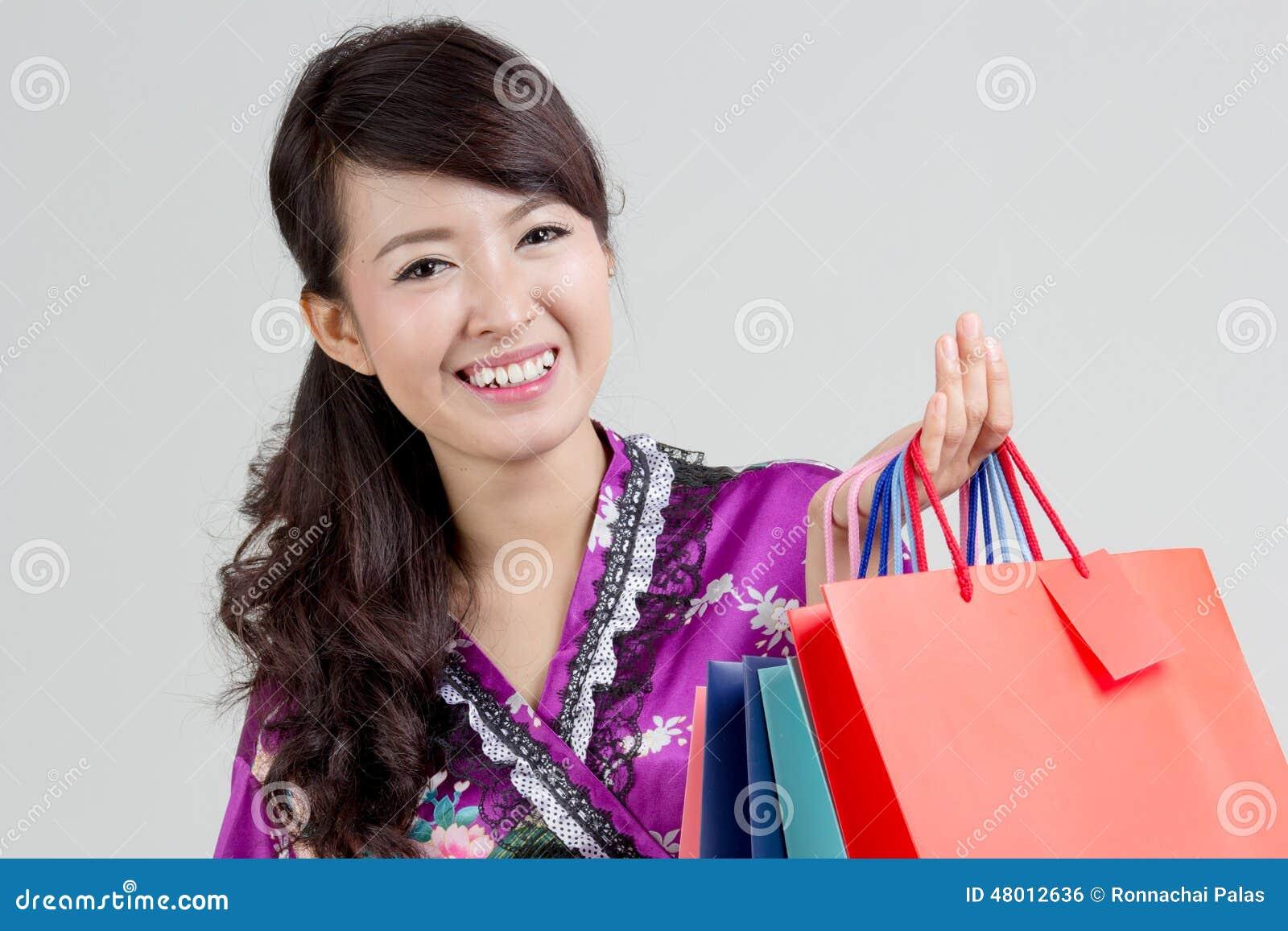 Asiatisk shoppingkvinna som rymmer färgrika shoppingpåsar