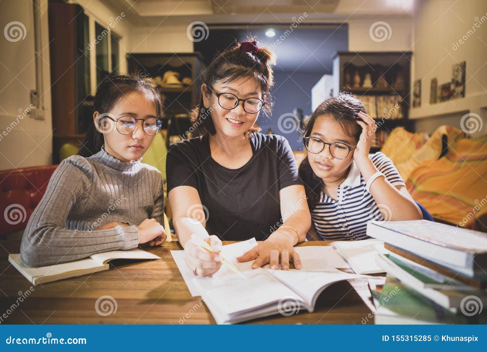 Asiatisk toothy le framsida för tonåringstudent- och kvinnalärare i modernt grupprum