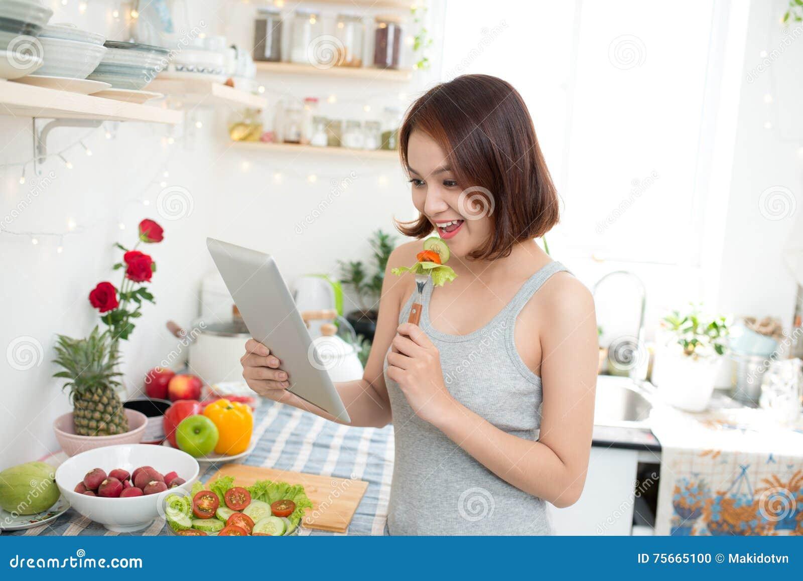 Asiatisk ung kvinna som äter sund mat och använder en minnestavlacompute