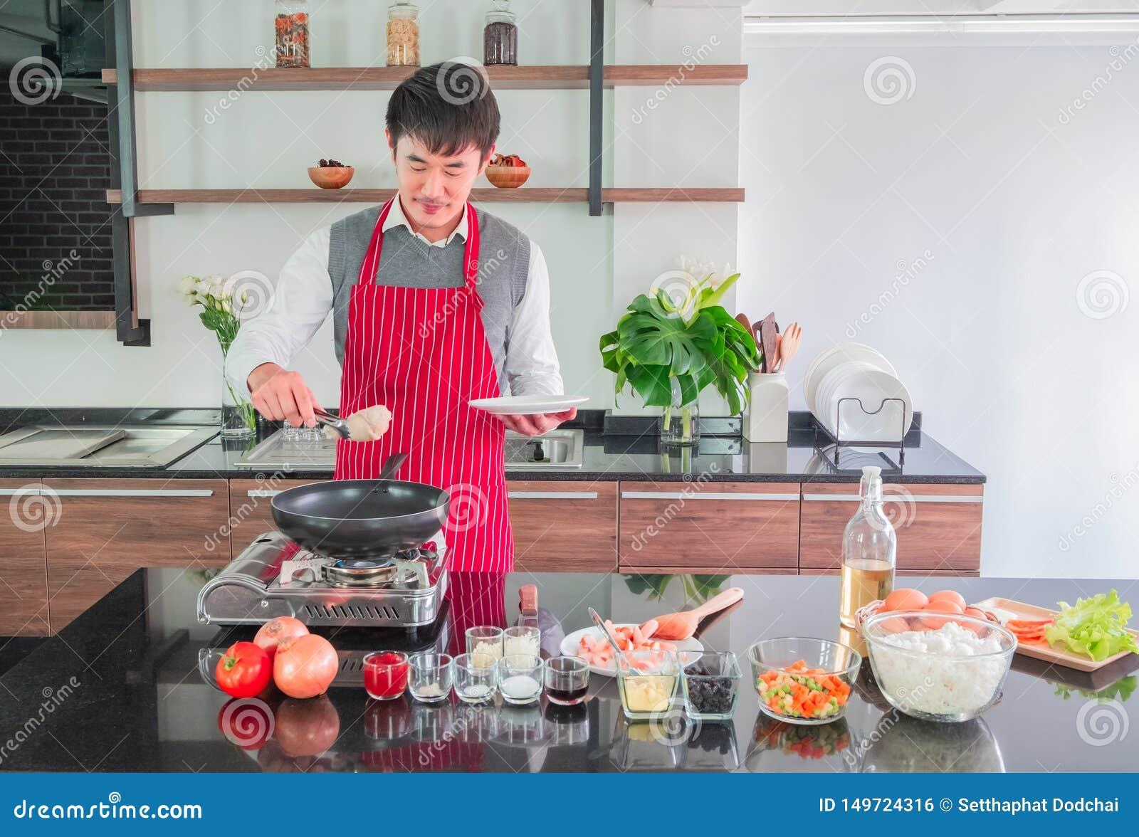 Asiatisk ung man i rött förkläde Laga mat för mat i köket hemma