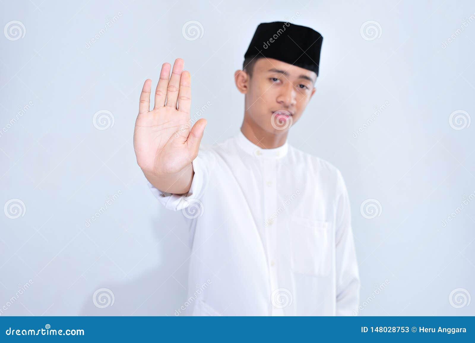 Asiatisk ung muslim man med den öppna handen som gör stopptecknet med det allvarliga och säkra uttryckt, försvargest
