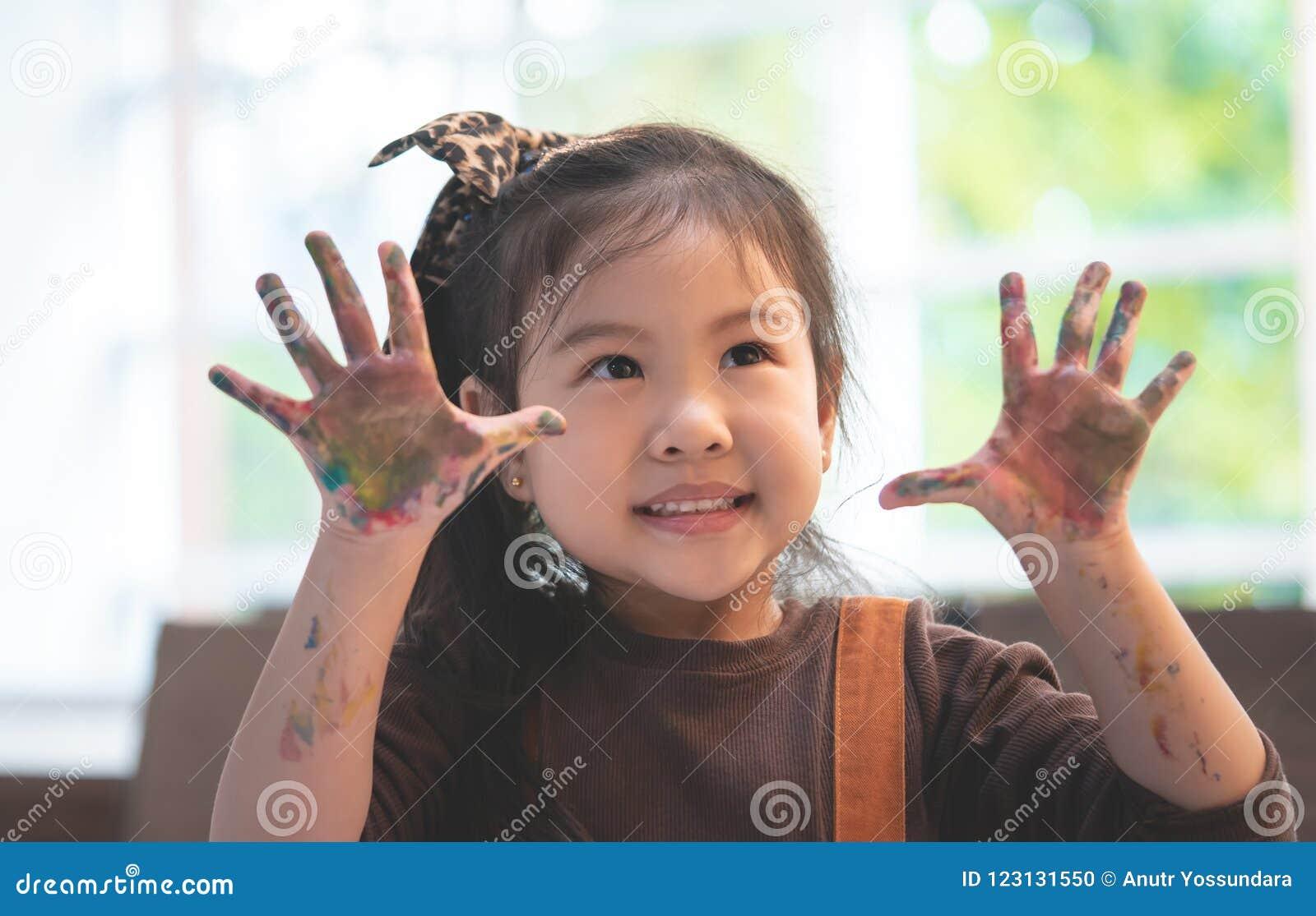 Asiatisk unge med den smutsiga målade handen i konstklassrum