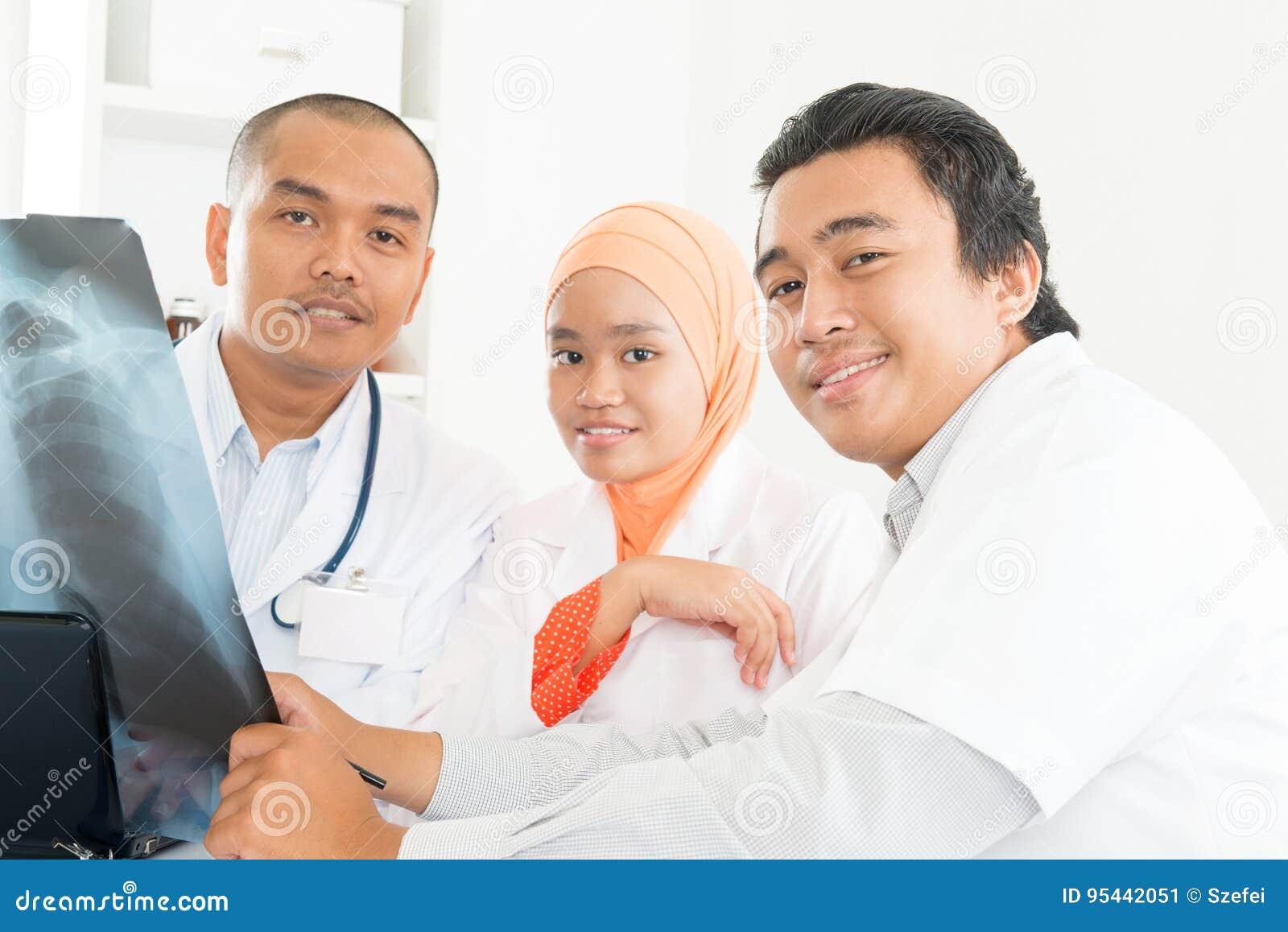 Asiatiska doktorer som diskuterar på röntgenstrålebild