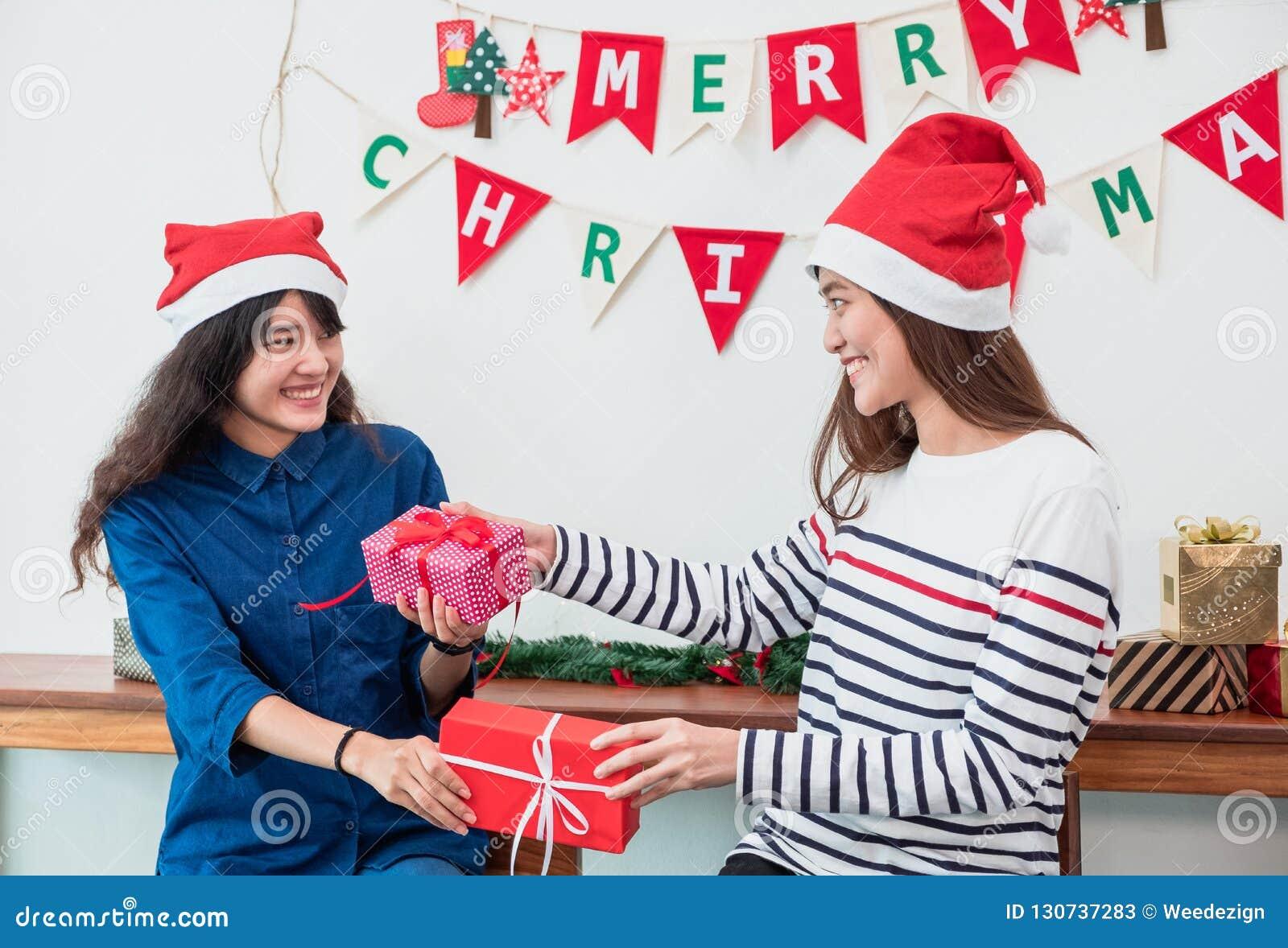 Asiatiska flickavänner bär den santa hatten i parti för glad jul och e