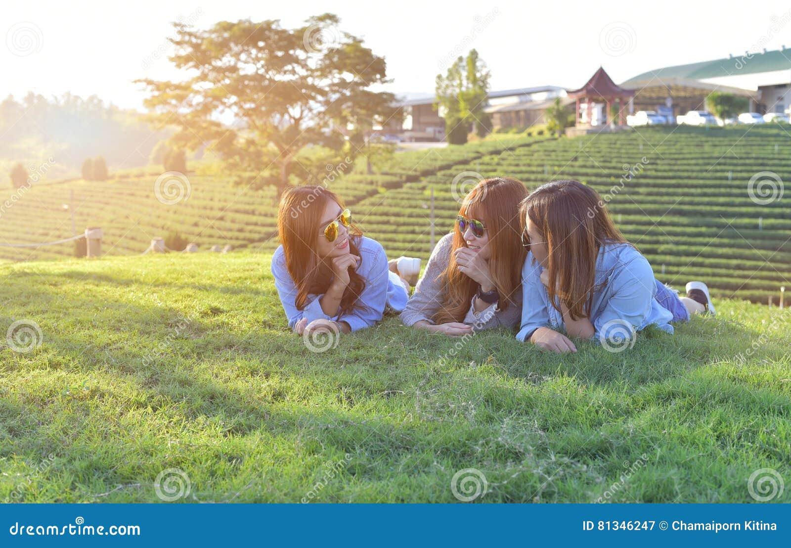 Asiatiska flickor som lägger på det gröna gräset under solljus, w