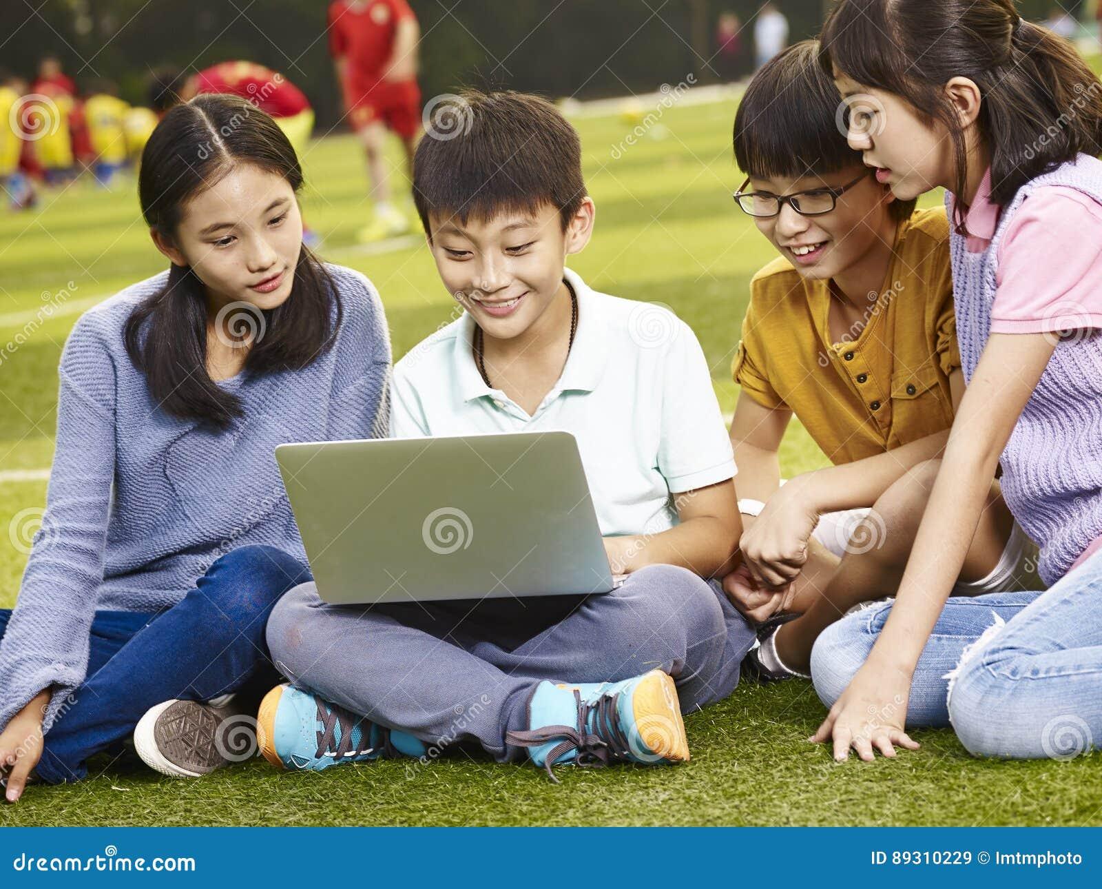 Asiatiska grundskolabarn som utomhus använder bärbara datorn
