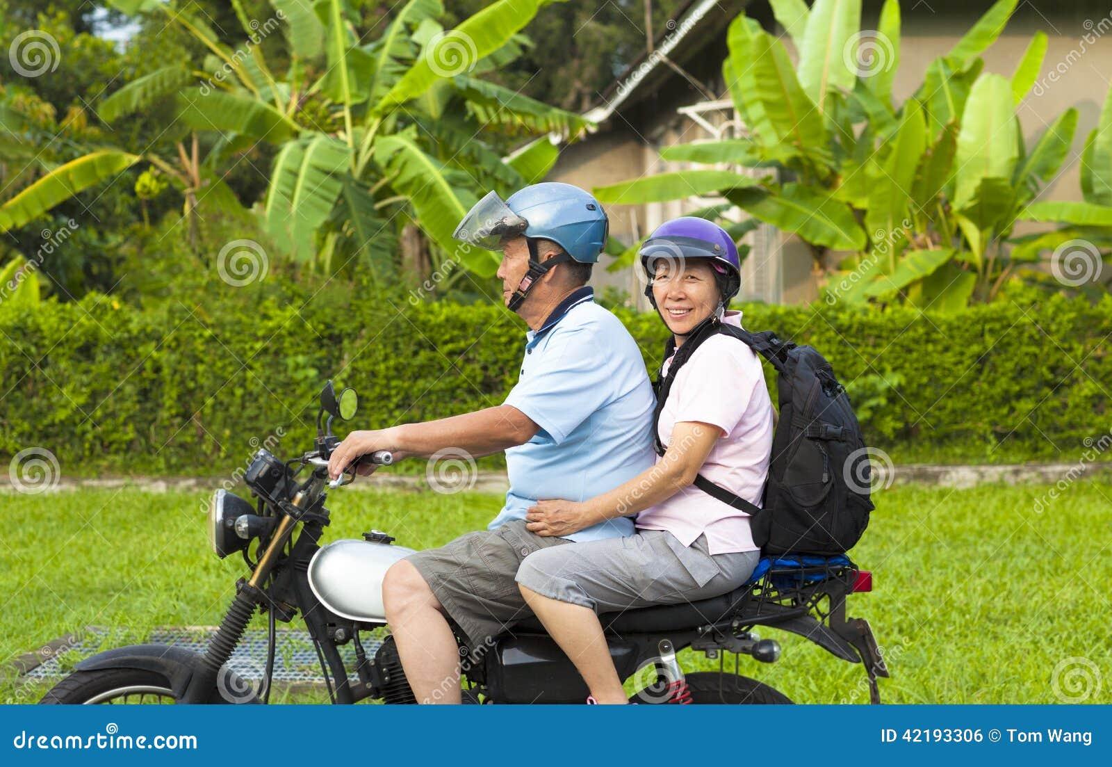 Asiatiska höga par som kör motorcykeln till loppet