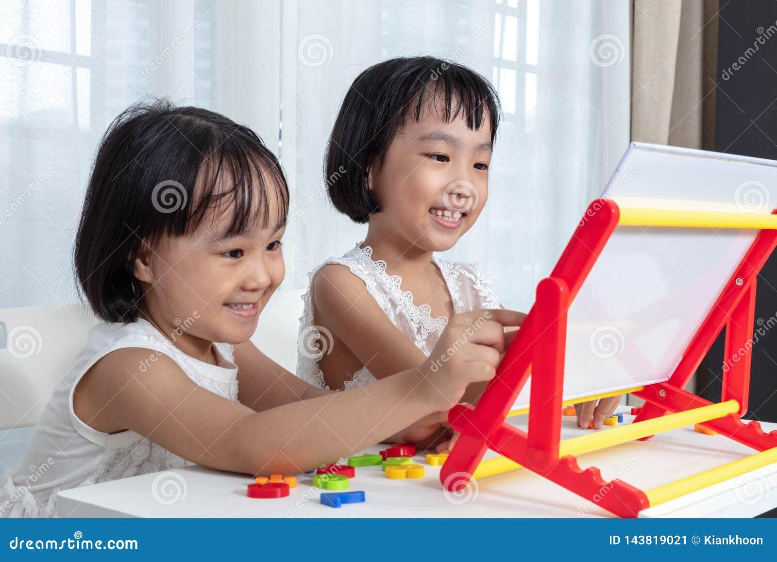 Asiatiska kinesiska små flickor som spelar leksaker