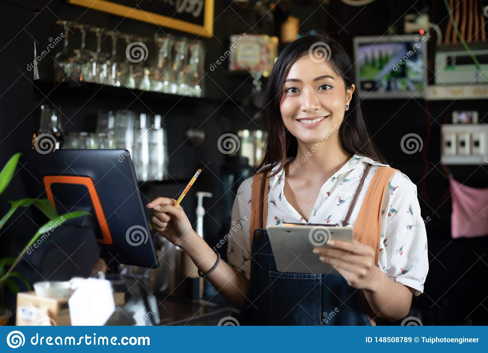 Asiatiska kvinnor Barista som ler och anv?nder kaffemaskinen i coffee shopr?knare - mat och drink f?r ?gare f?r sm? och medelstor