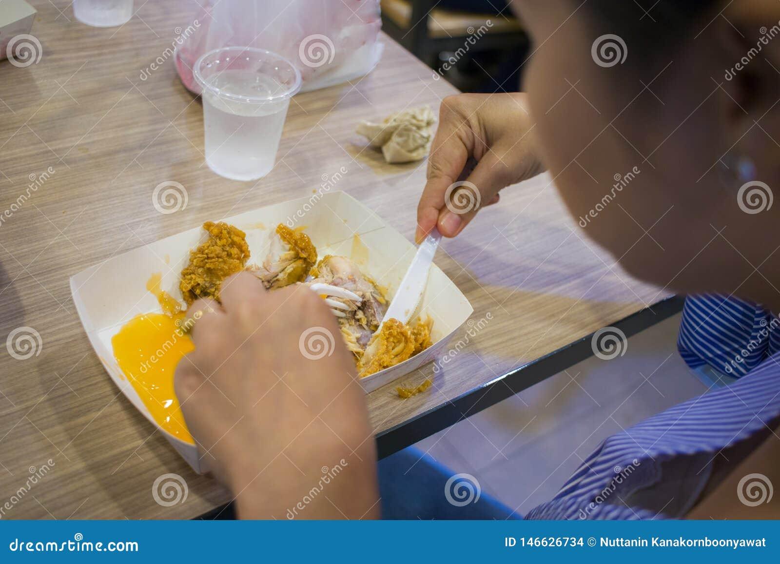 Asiatiska kvinnor som ?ter stekt kyckling, stekt kyckling f?r h?llen f?r fokuskvinnahanden f?r, ?ter, flickan med snabbmatbegrepp