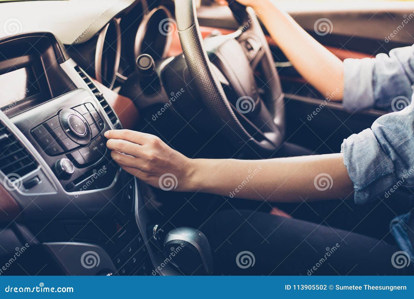Asiatiska kvinnor trycker på knappen på bilradion för att lyssna till musik