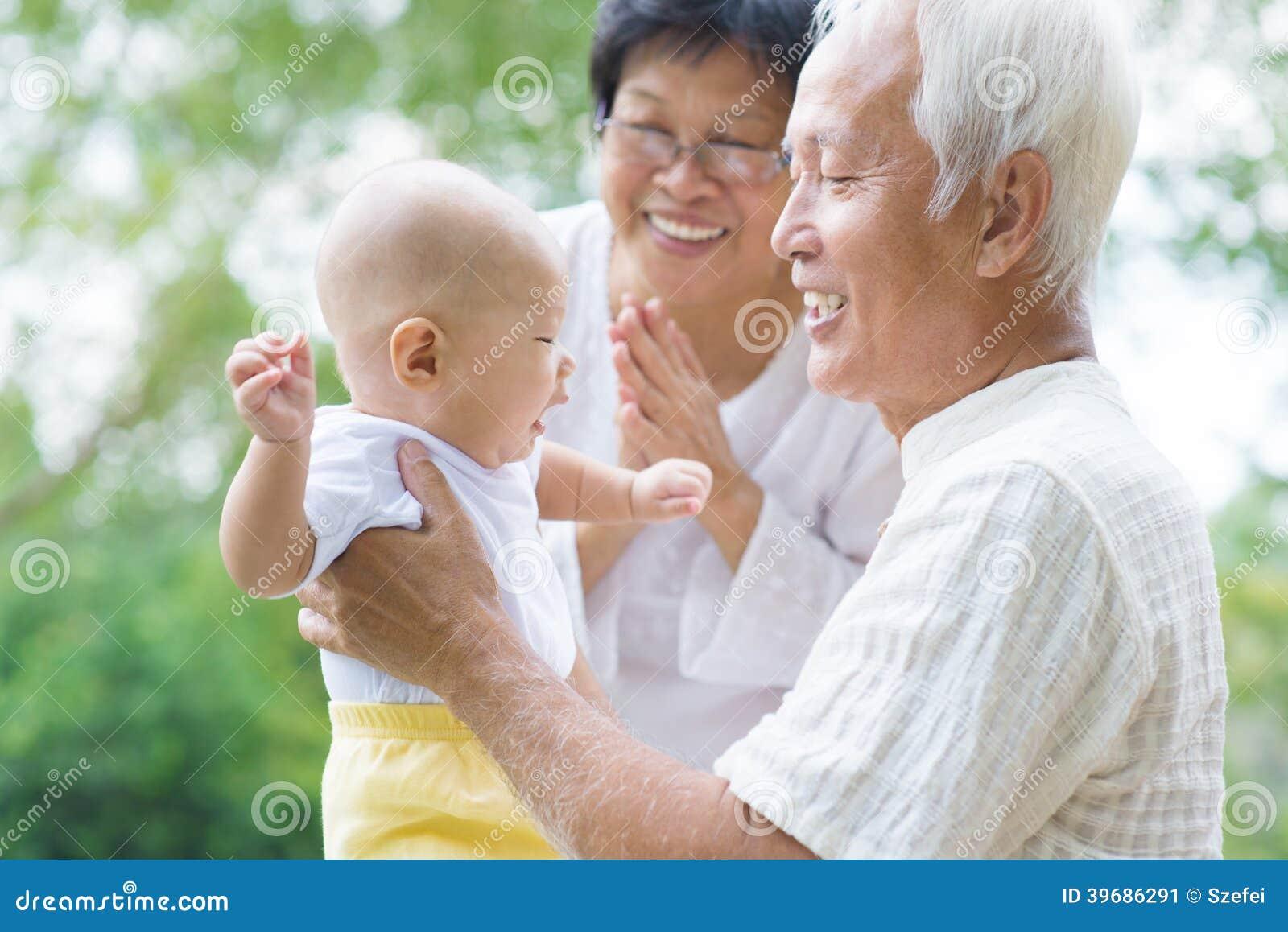 Asiatiska morföräldrar som spelar med sonsonen
