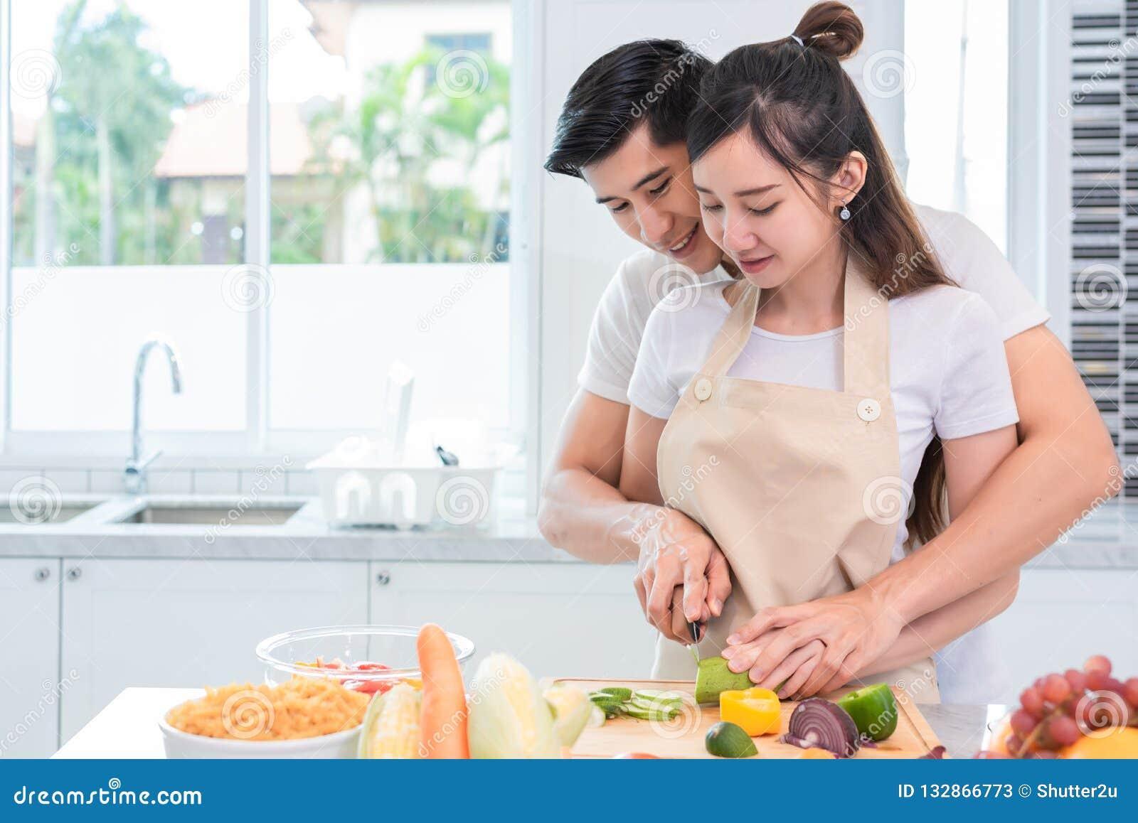Asiatiska par som tillsammans lagar mat och skivar grönsaken i kök
