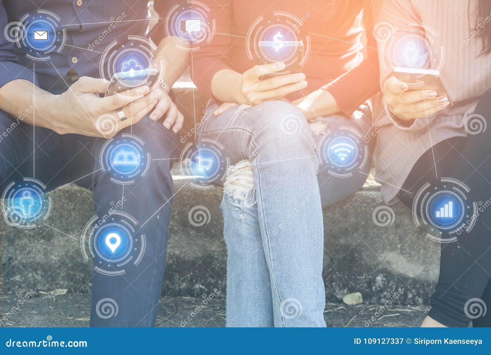 Asiatiska tonåriga vänner som sitter med den smarta telefonen i hand, förbinder till socialt massmedia med teknologinätverkande