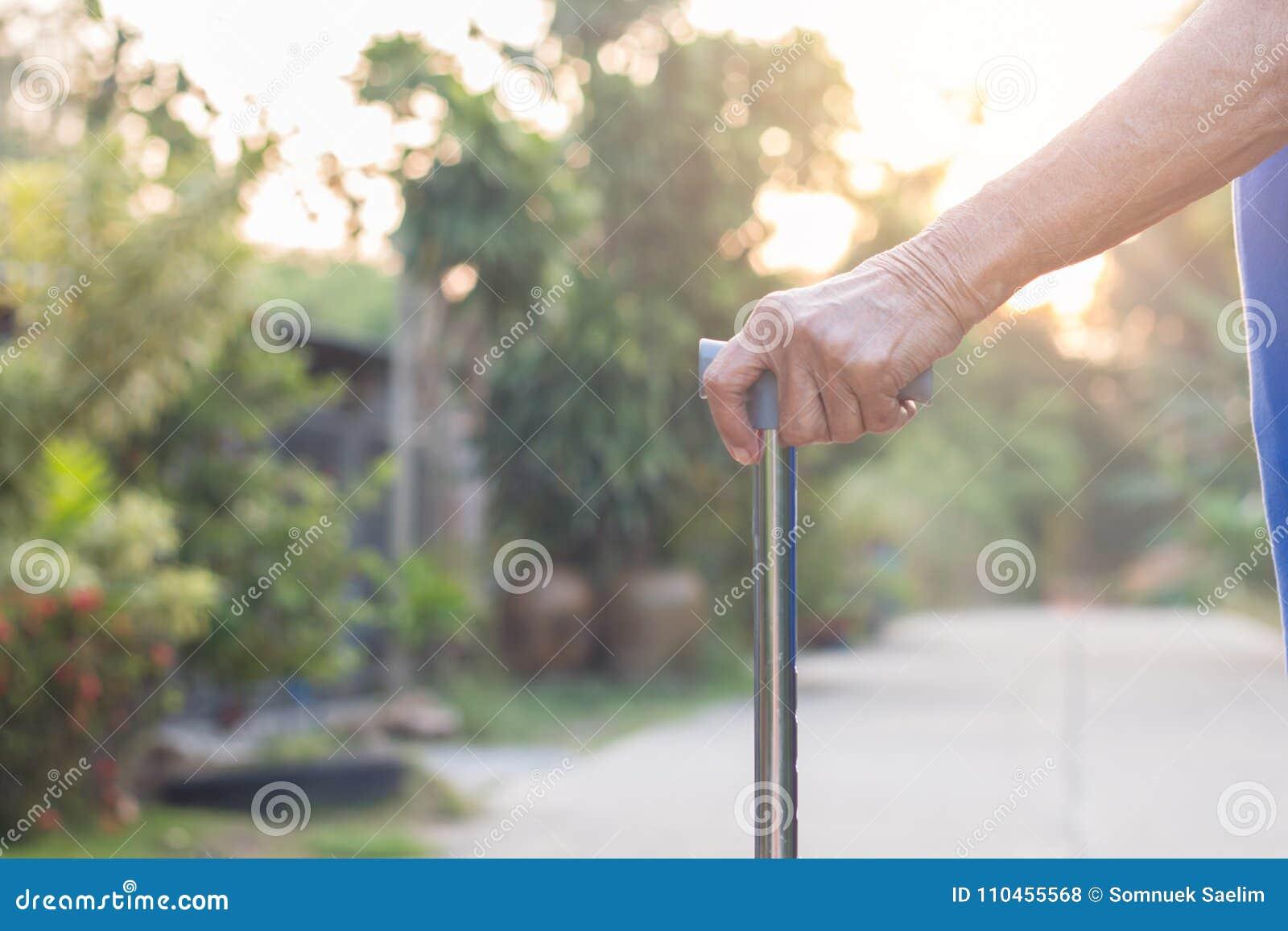 Asiatiskt anseende för gammal kvinna med hans händer på en gå pinne, hand