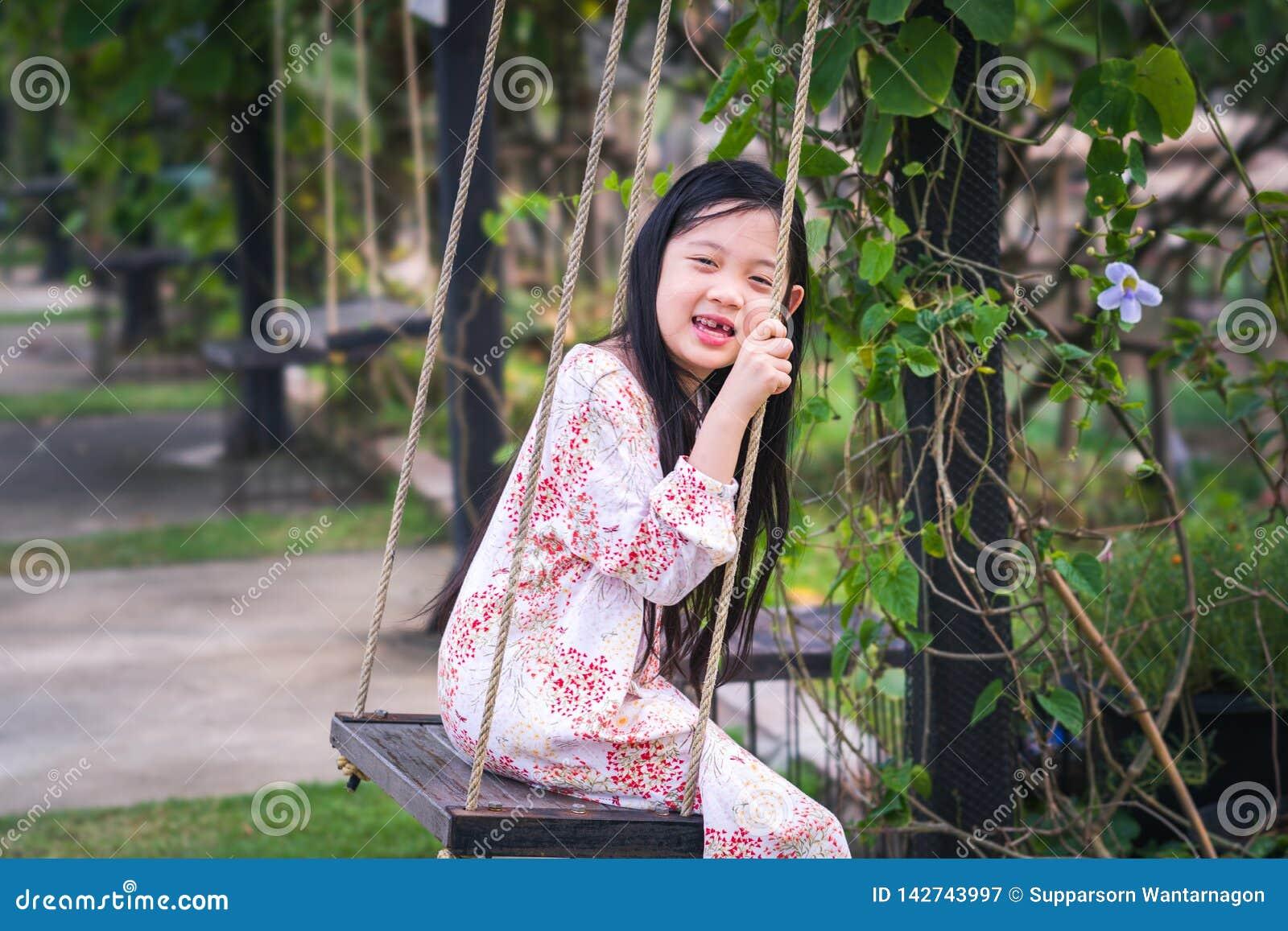 Asiatiskt barn på gunga i lekplats