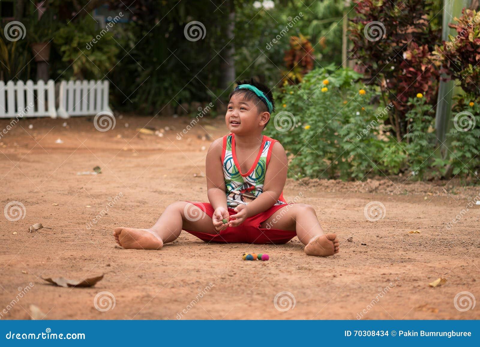 Asiatiskt barn som spelar med sand och bollen i lekplatsen